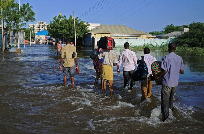 Residents walk through flooded streets in Beledweyne, north of Mogadishu on May 26, 2016. / AFP / MOHAMED ABDIWAHAB