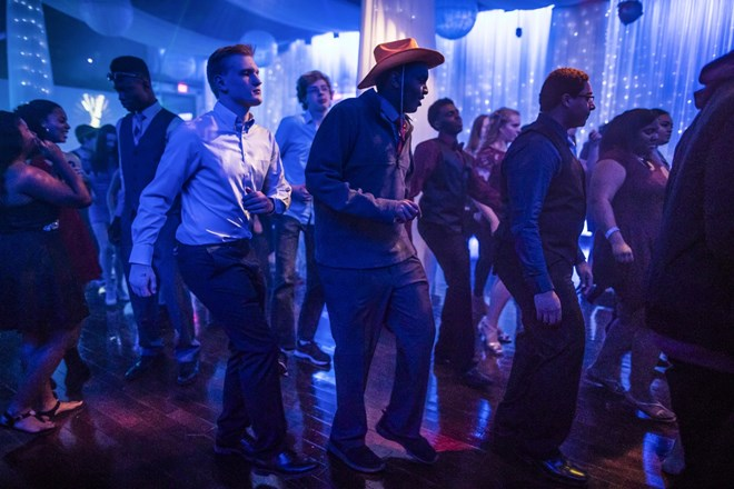 Mohamed Hassan, wearing a cowboy hat he had found at a photo booth, line-danced with fellow Roosevelt High School students at a school dance at the Profile Event Center in Minneapolis, Minn., on February 16, 2017. Renee Jones Schneider