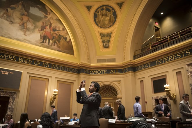 Dressed in a suit and tie, Mohamed Hassan took a picture of the Minnesota State Capitol Senate Chambers as he participated in a Youth in Government model assembly session on January 6, 2017, in St. Paul, Minn. Renee Jones Schneider