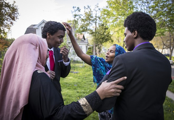 Mohamed Hassan's mother Amino A. Farah, left, and sister Fardowsa Hassan, in blue, doted over him and his brother Ali Hassan, right, in their suits as they came outside to take pictures with them before Mohamed's senior prom on May 6, 2017 at home in Columbia Heights, Minn. Renee Jones Schneider