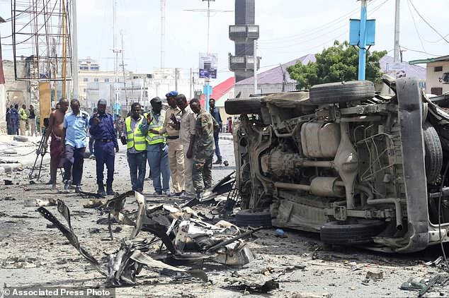 Somali forces watch a vehicle demolished by twin blast in Mogadishu on Saturday, July, 7, 208. At least nine people have been killed and many others injured in an ongoing attack at Somalia's interior ministry as security forces continued battling militants holed up inside, Somali officials say.(AP Photo/Mohamed Sheikh Nor)