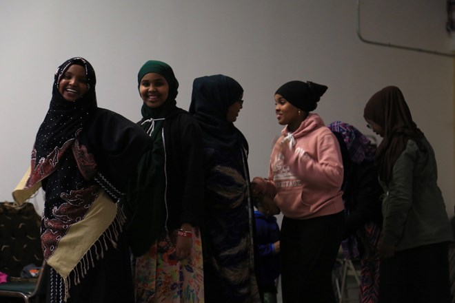 The girls in line wear uniquely patterned skirts as they dance. Esther doesn't worry too much about her daughters possibly being singled out because of their clothes. She said they live in a great neighborhood with a good community that understands the Muslim faith. (Photo by Ester Ouli Kim.)