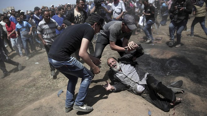 An elderly Palestinian man falls on the ground after being shot by Israeli troops during a deadly protest at the Gaza Strip's border with Israel, east of Khan Younis, Gaza Strip, Monday, May 14, 2018 - Khalil Hamra / AP
